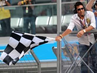 Sachin Tendulkar waves chequered flag at the inaugural Indian Grand Prix